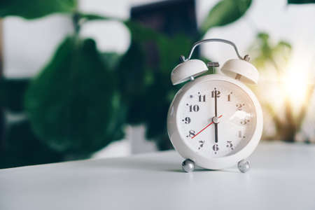 Selective focus of alarm clock show 6 o'clock or 6 a.m. on table with nature bokeh background. Time in life concept. Early bird person.