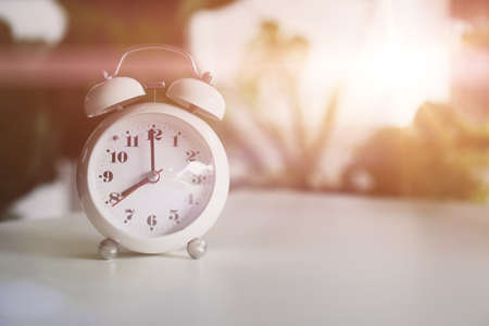 Selective focus of alarm clock show 8 o'clock or 8 a.m. on table with nature bokeh background. Time in life concept.