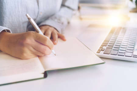 Woman is writing in planner notebook while using laptop to work or plan with workspace at home. Education business lifestyle concept.