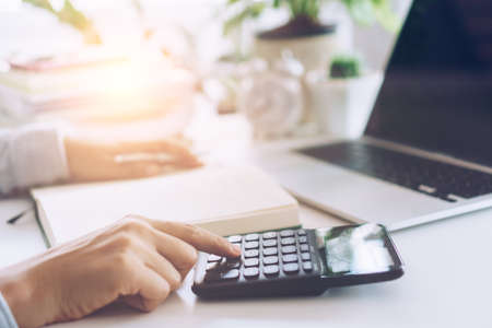 Woman is working on clean nature workspace at home with laptop, planner notebook and calculator. Business finance office concept.
