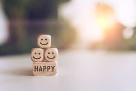 Smile face and Happy word on wooden cube. Optimistic person or people feeling inside.