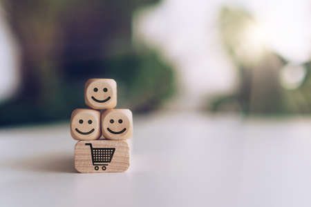 Smile face and cart icon on wooden cube. Optimistic person or people feeling inside and service rating when shopping, satisfaction concept in business. 免版税图像