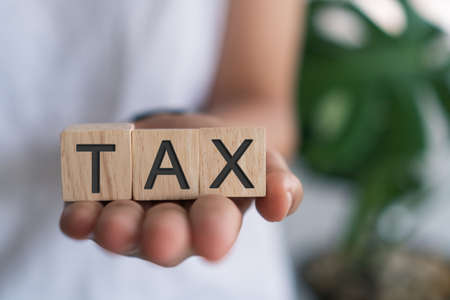 Tax word on wooden cube background. Business financial loan property concept.