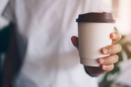 Hand hold a cup of coffee with sunlight flare beautiful copy space background. Wake up caffeine intake in morning time.