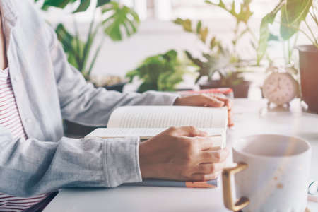 Woman is reading book in workspace area with nature background feeling relax and peaceful environment. Education business concept.