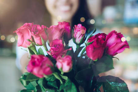 Woman happy hold pink roses recieve from someone in love on Valentine's day.