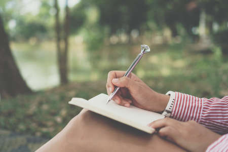 Woman hand writing down in small white memo notebook for take a note not to forget or to do list plan for future in public park.