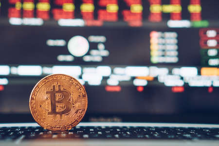Bitcoin crypto currency digital gold money coin replica on laptop with trading stock financial on screen. Business finance concept.