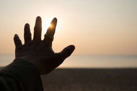 Hand reach out to sunset sky beach sand nature background. Relax and rest in vacation time.