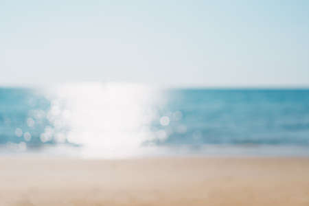 Blur tropical nature clean beach and white sand in summer season with sun light blue sky background.