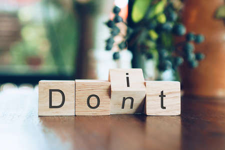 Do it or don't on wooden cube on table. Key to success concept background.
