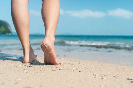 Woman feet walk slow life and relax on sand tropical beach with blue sky background. Vacation and holiday concept.