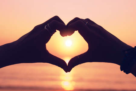 Woman hand do heart shape on sunset sky and bokeh background. love valentine day concept. 免版税图像