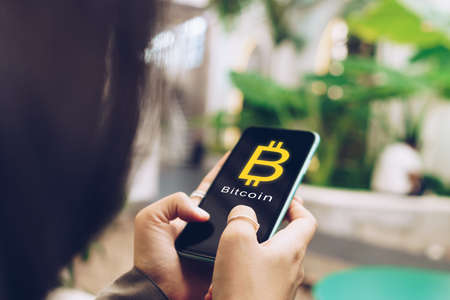 Woman use gadget mobile smartphone earn money online buy bitcoin with sign icon pop up. Business fintech technology on smartphone concept.