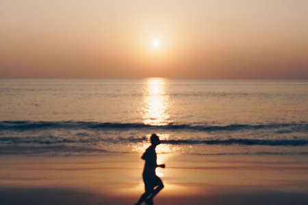 Tropical nature clean beach sunset sky time with blur silhouette man running sun light background.