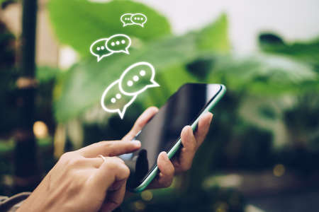 People hand using smartphone typing, chatting or text  messages in chat icons pop up. Social media maketing technology concept. Vintage soft color tone background. 免版税图像