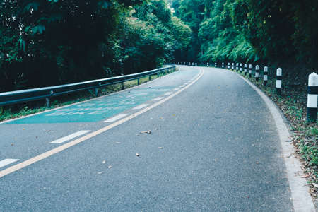 Road with bicycle lane in the country with nature surrounding background.