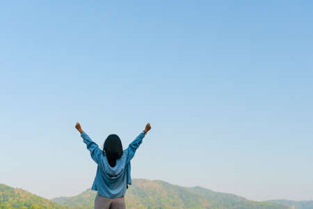 Woman rise hands up to sky freedom concept with blue sky and summer field mountain background. 免版税图像