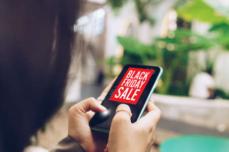 Women hand using smartphone do online selling on black friday sale for people shopping online with chat box, cart, dollar icons pop up. Social media maketing concept. 免版税图像