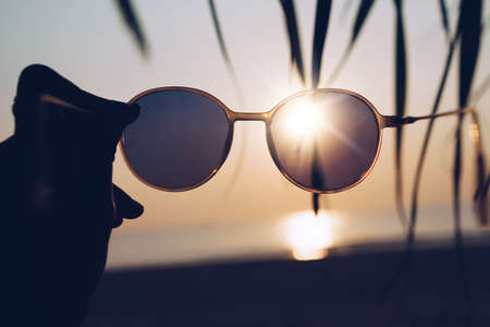 Woman hold sunglasses on sunset beach summer background with sunlight and flare. 免版税图像 - 164792129