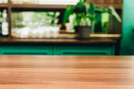 Selective focus of wooden table with blur coffee and restutant cafe with customers background.