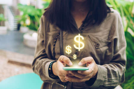 Woman use gadget mobile smartphone earn money online with dollar icon pop up. Business fintech technology on smartphone concept. 免版税图像