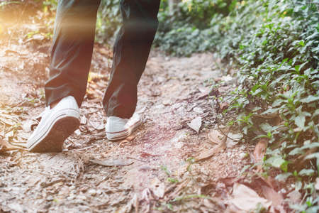 Man is walking into the wood or jungle nature walk way with sunlight.Slow life lifestyle and exercise.