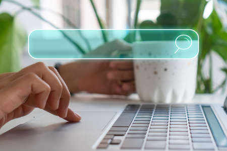 People hand using laptop or computor searching for information in internet online society web with search box icon and copyspace.