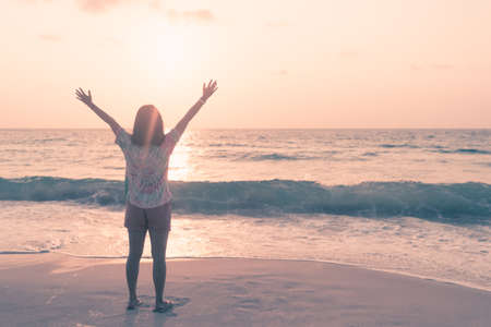 Woman rise hands up to sky travel around the world with summer beach freedom and relax life.
