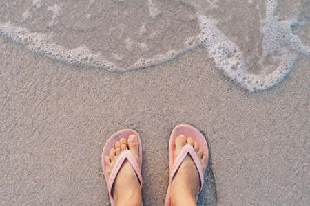 Woman feet wear slippers stand on sand tropical beach with sea water splash background.