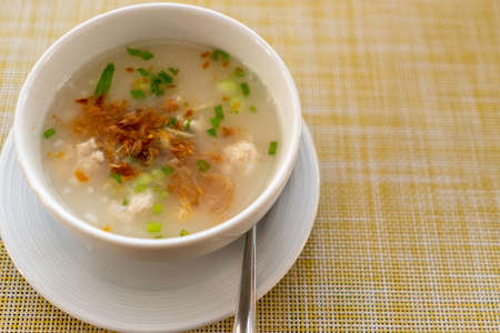 Thai style breakfast pork rice soup with egg on wood table. Copy space put your text on background.