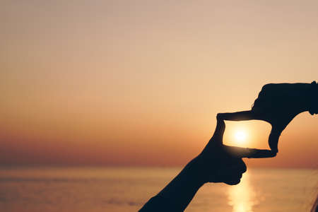 Selective focus of woman hands making frame by finger gesture with sunrise on mountain, Female capture sunrise or sunlight outdoor. Future planning concept. Imagens