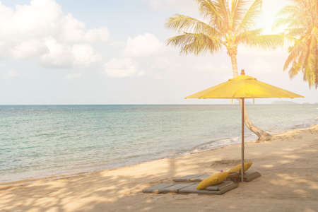 Umbrella and chair at tropical summer beach background with copy space blue sky. Imagens