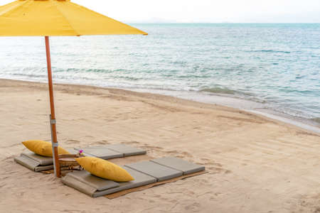 Umbrella and chair at tropical summer beach background with copy space blue sky. 免版税图像