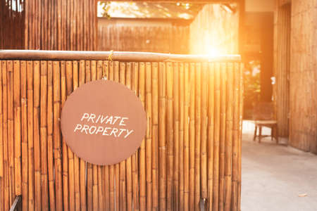 A Sign board of private property hang on door of business shop with wooden background