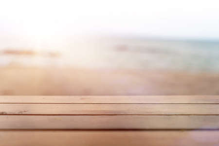 Selective focus of old wood table with blur beautiful beach background for display your product.