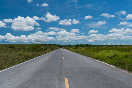 Small country road or street with blue sky background.