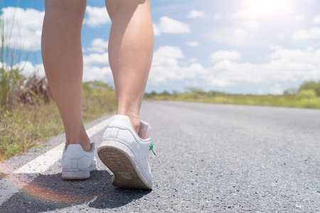 Woman is walking on small country road street with blue sky background. Imagens