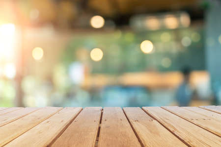 Selective focus of wooden table with blur coffee and restutant cafe with customers background. Reklamní fotografie