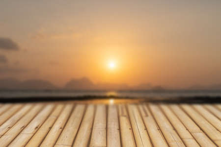 Selective focus of old wood table with blur beautiful beach for display your product.