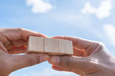 Blank wooden cube that you can put text or icon on in hand hold background