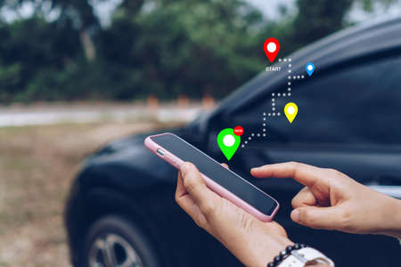 Woman use smartphone to look up map plan route for travel. Road trip concept. Stock Photo