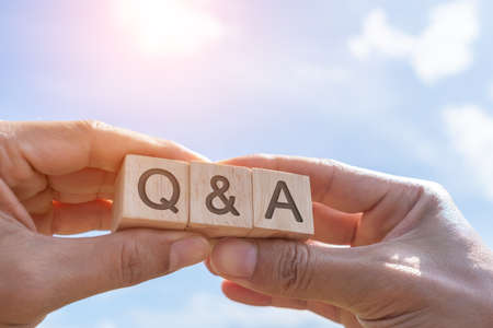Q and A alphabet on wooden cube in hand hold with background. Question and answer meaning concept.
