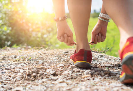 Woman wear running shoe on to walking and running on nature green background.Health exercise concept.