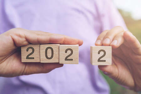 Hand hold wooden cubes 2022 background, copy space. Goal concept, action plan, strategy, new year or business vision. Stock Photo