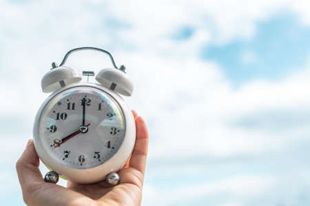 Selective focus of alarm clock with nature bokeh background. lifestyle  productive life concept.