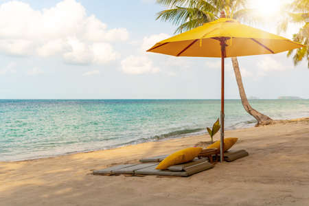 Umbrella and chair at tropical summer beach background with copy space blue sky. Stock Photo