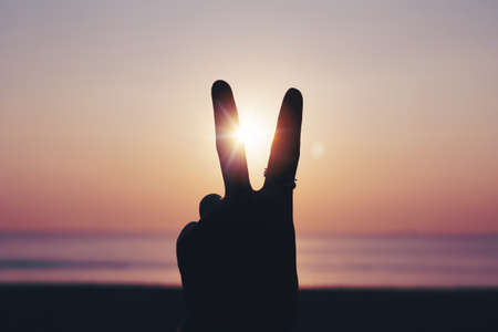 Peace out or fighting metaphor two fingers hand sign in front of a sunset. Happy people enjoying nature.