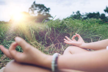 Woman practicing yoga lesson, breathing, meditating exercise, outdoor in grass field. Well being, wellness concept