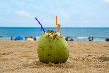 coconut with straws on beach sand